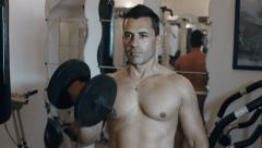 Handsom adult man uses a weight exercising  at a home gym to stay fit and stren Stock Footage