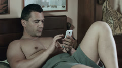 Topless man using a cell phone while laying on bed: bare-chested Stock Footage