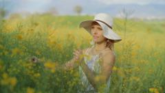 A portrait of a happy woman with white hat, yellow rape field - stock footage