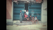 Group of children sitting in a large opened doorway while man walking away Stock Footage
