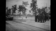 Officers looking at military tank rolling on road Stock Footage