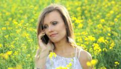 Happy woman in a yellow rape field laughing on the mobile phone - stock footage