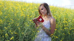 Pretty blonde girl in a yellow rape field with a pen and a note-book writing Stock Footage