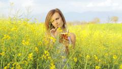 Young caucasian woman in yellow rape field - stock footage