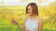 Stock Video Footage of Beautiful Woman in white dress holding a bunch of rape flowers