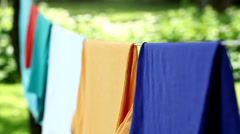 Woman taking dry clothes from cord - stock footage