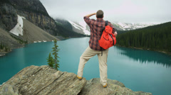 Male hiker viewing turquoise Lake Moraine, Alberta, Canada - stock footage