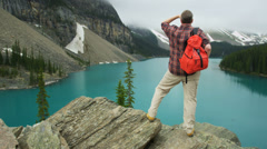 Male hiker enjoying majestic scenery, Lake Moraine, Canada - stock footage