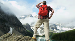 Male hiker viewing cloud covered Peaks Lake Moraine, Canada - stock footage