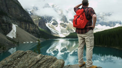 Lake Moraine male viewing coniferous forests Rocky Mountains, Canada - stock footage