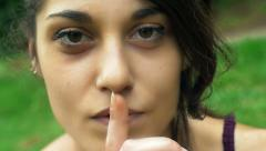 Cute young girl saying to do silence with her finger Stock Footage