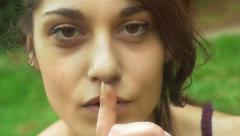 Young cute girl saying to do silence with her finger: outdoor, park, portrait Stock Footage