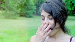 Tired sleepy young girl yawns in the park: get bored drowsy Stock Footage