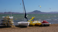 Stock Video Footage of Boats and surfboards on beach and kitesurfers riding in sea. La Manga, Spain.