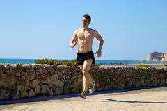 handsome muscular athlete jogging in front of ocean and castle in italy - stock photo