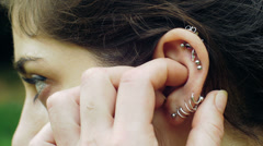 young cute girl touching her ear piercing: ear, earring, play with  - stock footage