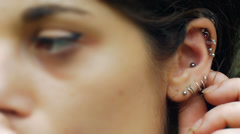 young cute girl touching her ear piercing: ear, earring, 4k footage - stock footage