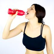 Sporty young woman drinking after fitness Stock Photos
