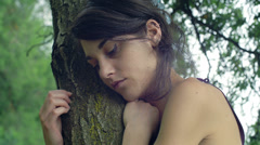 Upset young person pretty beautiful leaning against a tree. Close up 4k footage Stock Footage