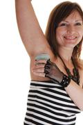 girl putting deodorant on. - stock photo
