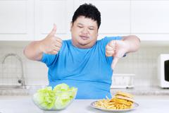 Stock Photo of man showing healthy and unhealthy food