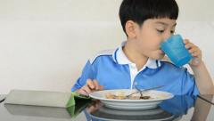 Little asian boy eating fried rice and playing tablet computer . - stock footage