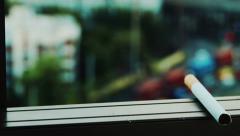 Cigarette sitting on window seal Stock Footage