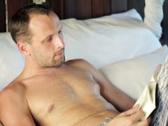 Young man reading book on comfortable bed NTSC Stock Footage