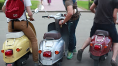 Young people on scooters on city street Stock Footage