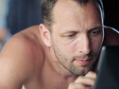 Young man with tablet computer lying on comfortable bed NTSC Stock Footage