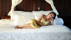 Sexy woman lying on bed and talking on cellphone HD - stock footage