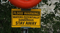 Flood warning sign with river in background. Stock Footage
