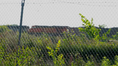 Train passing by behind chain link fence Stock Footage