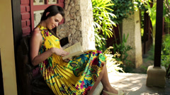 Woman reading book on bench in front of country house HD Stock Footage