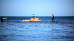 Fishermans at the sea standing on stones go fishing. Video in Koh Samui Thailand Stock Footage