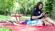 Stock Video Footage of young mother using wifi tablet with little baby sleeping in the natural park