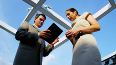 Caucasian managers using internet on tablet on rooftop office - stock footage