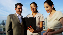 Diverse colleagues planning outdoors funds on tablet overlooking Manhattan - stock footage