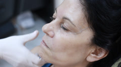Cosmetic treatment in a clinic woman getting a botox injection to the face Stock Footage