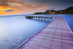 Wood bridge piers with nobody and smoothy sea water against beautiful sun ris Stock Photos