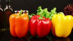 DOLLY: Three varieties of peppers on dark kitchen table Stock Footage