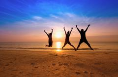 family jumping team on the beach on beautiful sunrise silhouette shot,happy f - stock photo