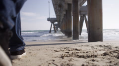 Man Walks toward Ocean at Pier on Sand at Beach under Dock in 4K - stock footage