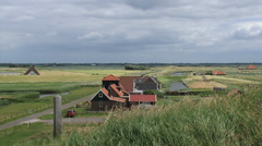 Farmhouse and agricultural fields in Dutch polder behind seawall near Petten Stock Footage