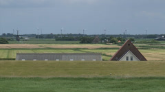 Rooftop of Farmhouse behind dike, zoom out Dutch polder behind seawall Stock Footage