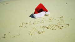 Santa Hat Beside Christmas Greeting  in Sand Stock Footage