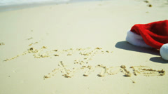 Santa Hat Beside Christmas Greeting  in Sand - stock footage