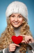 Girl in winter clothes giving heart. concept of valentine's day Stock Photos