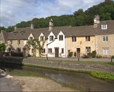 Castle Combe village  - pan street, houses along Bybrook River Stock Footage