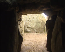 View from middle aisle to the entrance of a prehistoric burial mound, tilt up Stock Footage